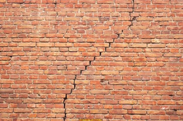 Mur de brique rouge fissuré