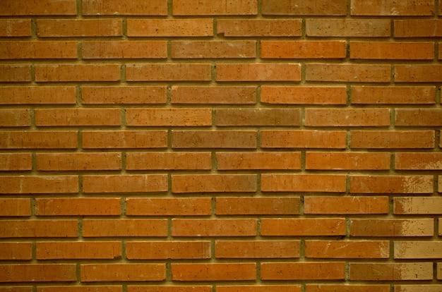 Mur de brique rouge texture de fond plein cadre avec des rangées de briques sur une façade de bâtiment extérieur.
