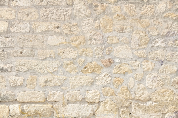 Mur de briques accidenté dans des couleurs claires
