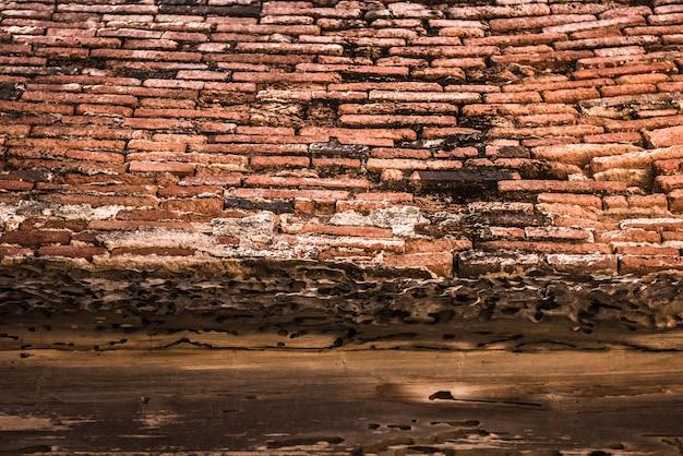 Mur de briques anciennes et poutres en bois.