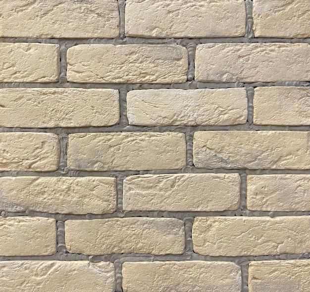Mur de briques beiges avec coutures grises de carreaux décoratifs pour la décoration murale. fond, texture