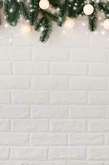 Mur de briques blanches avec des branches de sapin et des lumières de noël en forme de boules blanches.