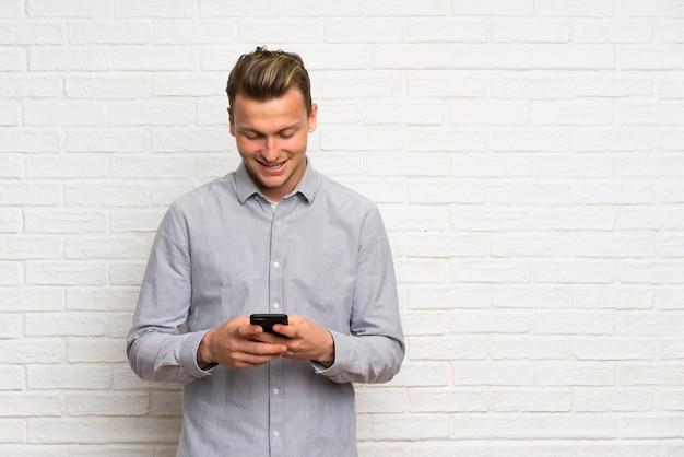 Mur de briques blanches homme blond envoie un message avec le mobile