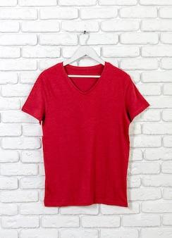 Mur de briques blanchies à la chaux avec t-shirt sur cintre