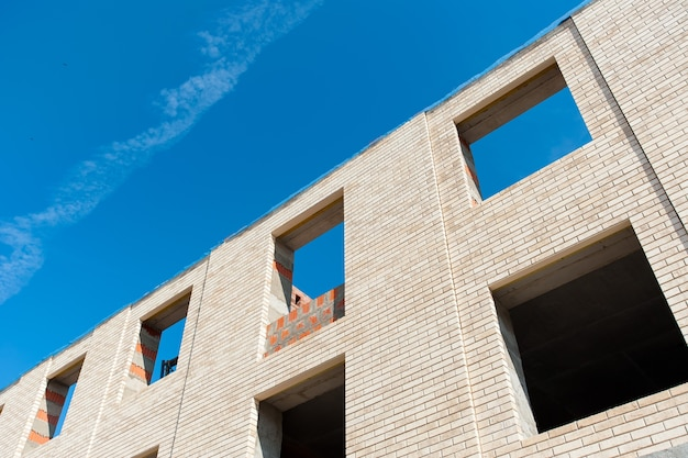 Un mur de briques brunes contre un ciel bleu