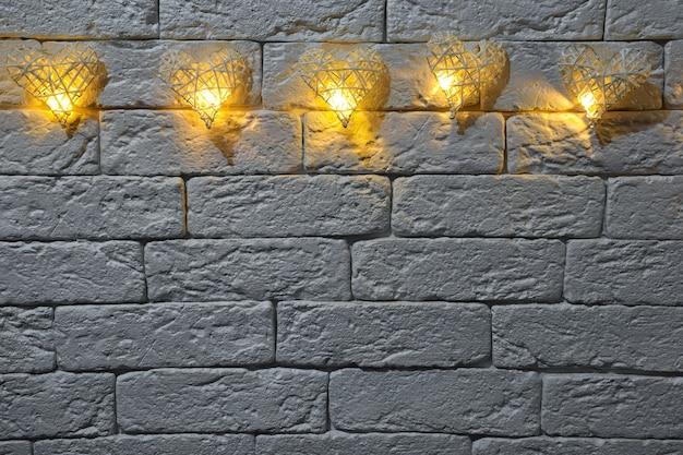 Sur le mur de briques décoratives, il y a cinq cœurs décoratifs en osier avec des ampoules faites à la main. en bas il y a une place pour les inscriptions pour les différentes fêtes.