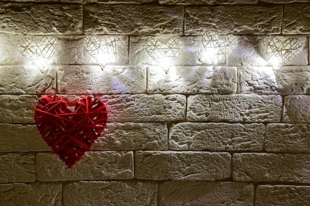 Sur le mur de briques décoratives, il y a cinq cœurs en osier avec des ampoules faites à la main. en bas à gauche, en dessous d'eux se trouve un grand cœur. il y a une place sur la droite pour les inscriptions pour les différents jours fériés.