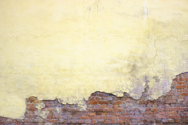 Mur de briques avec du plâtre endommagé