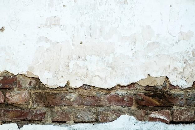 Mur de briques endommagé, plâtre fissuré, fond texturé