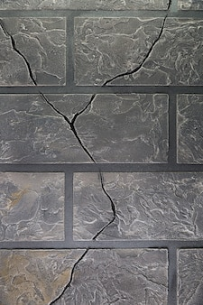 Mur avec des briques et des fissures
