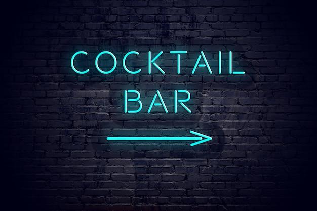 Mur de briques avec flèche au néon et signe bar à cocktails.