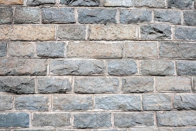 Un mur de briques de granit rugueux avec du coulis de ciment entre eux
