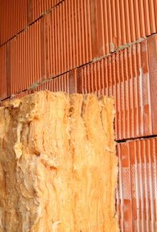 Mur de briques et laine d'isolation. immeuble avec isolation des murs creux. fermer.
