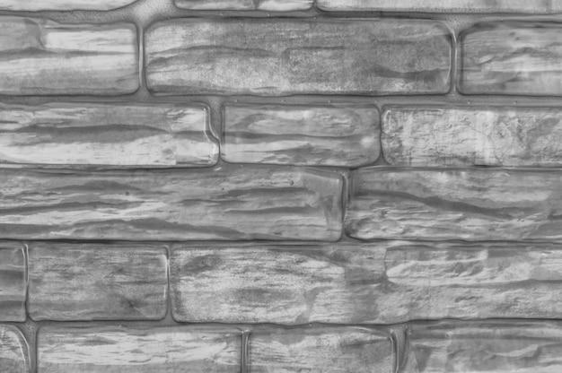 Le mur de briques de la maison est noir et blanc. fermer. arrière-plan flou