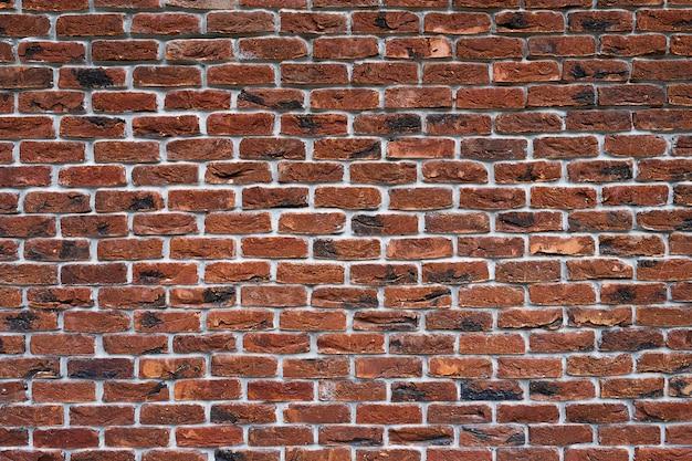 Mur de briques rouges la façade de l'immeuble avec du nouveau plâtre. maçonnerie. contexte. texture.