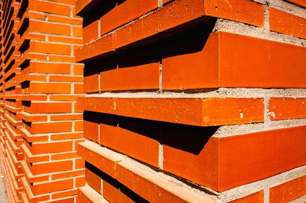 Mur de briques rouges intense au soleil.