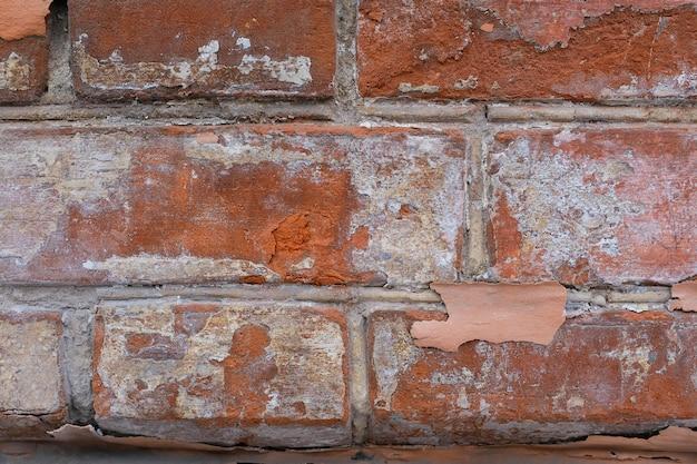 Mur de briques rouges à la peinture blanche.