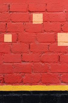 Mur de briques rouges avec des taches jaunes