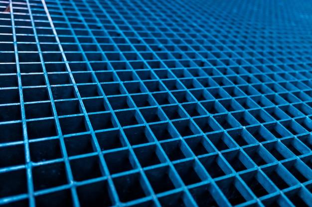 Mur de carrés d'une maille métallique bleue.