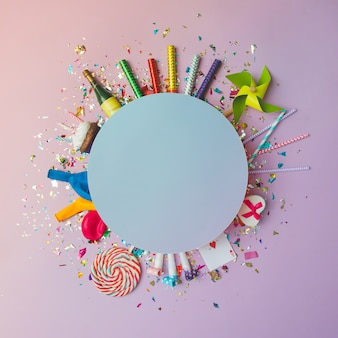 Mur de célébration coloré avec divers confettis de fête, ballons, banderoles, feux d'artifice et décoration sur mur rose. mise à plat.
