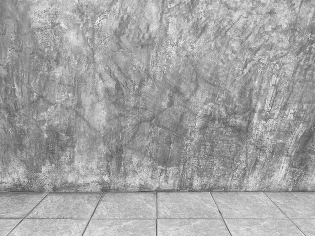 Mur de ciment et fond de plancher en céramique carré.