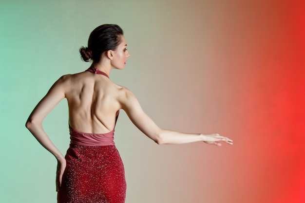 Mur coloré, néons, prise de vue en studio. portrait d'une jeune femme brune élégante