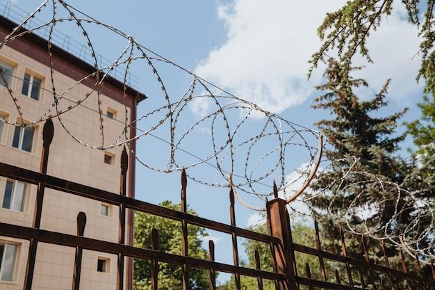 Mur de construction derrière la barrière de fil de fer barbelé avec de beaux nuages célestes