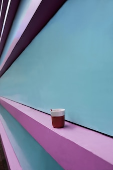 Mur de couleur rose et turquoise entrant en perspective. il y a une tasse de café rose sur le trottoir