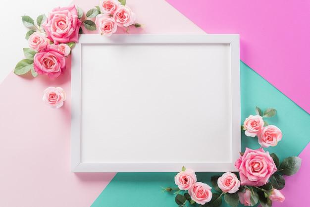Mur de couleurs pastel avec cadre photo et fleurs rose rose