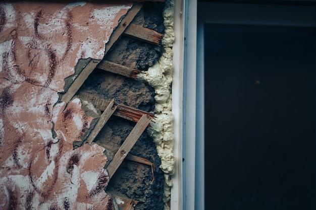 Mur en détresse avec des trous dans le plâtre et la latte de bois