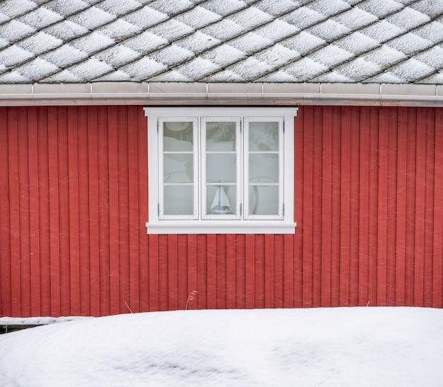 Mur extérieur en bois rouge avec fenêtre et toit