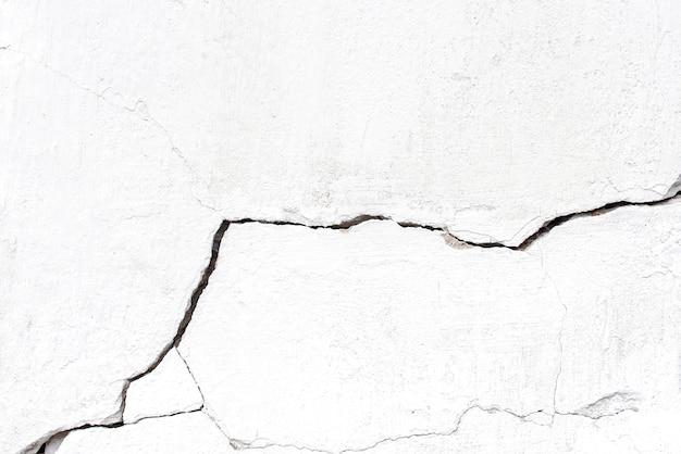 Mur fissuré en béton blanc avec grande fissure, arrière-plan ou texture