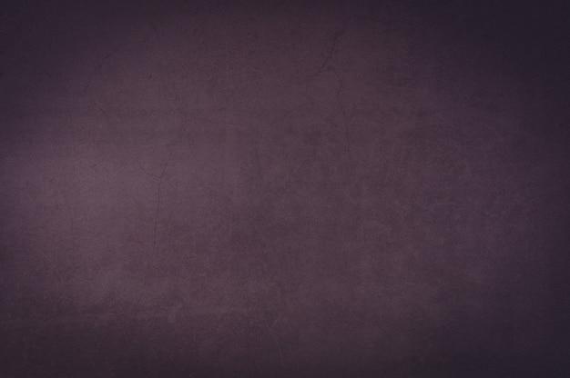 Mur de fond de vieux plâtre texturé violet.