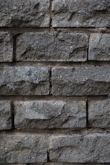Mur gris recouvert de dalles de pierre brute