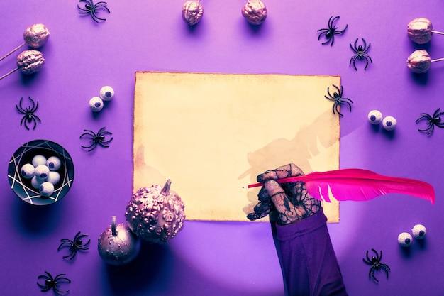 Mur d'halloween créatif en violet, rose et noir. sorcière en gants de maille noire écrit sur parchemin avec plume. mise à plat avec des araignées, des citrouilles roses et des yeux en chocolat, copie-espace