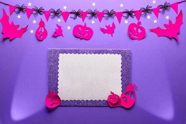 Mur d'halloween créatif en violet, rouge et noir, à plat avec copie-espace. projecteurs, figurines en papier de chauves-souris et citrouilles jack lanterne, guirlande d'araignées et papier avec copie-espace.