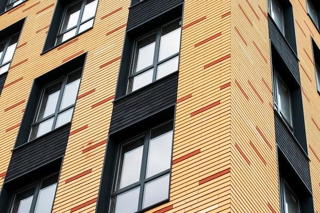 Le mur d'un immeuble de plusieurs étages en brique avec des fenêtres transparentes. motif abstrait géométrique. texture de façade de maison, arrière-plan.