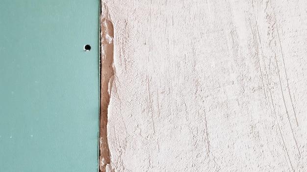 Mur inachevé dans un bâtiment en construction fait de plaques de plâtre. une partie du mur est recouverte de plaques de plâtre. les cloisons sèches sont boulonnées au mur en prévision du plâtre.