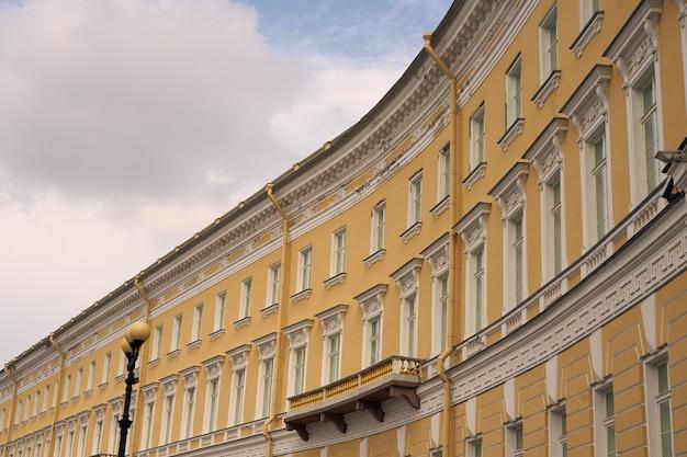 Le mur jaune d'un ancien immeuble de plusieurs étages avec un ciel nuageux en arrière-plan.