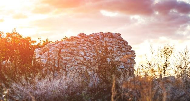Mur d'une maison en ruine sur fond de nuages sombres pendant le coucher du soleil_