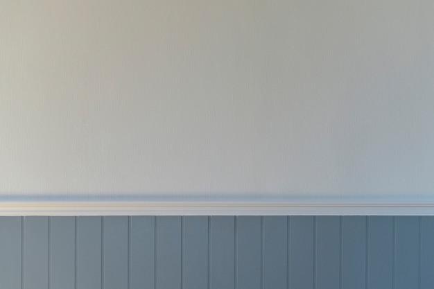 Le mur de la maison de style vintage a un mur blanc avec une texture et la partie inférieure est en lattes bleu-gris.