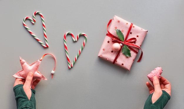 Mur de noël festif avec une boîte cadeau rose enveloppée avec une boule et une feuille de houx, des coeurs en cannes de bonbon, des mains féminines avec un bijou en étoile et du pain d'épice. mise à plat décorative sur papier gris