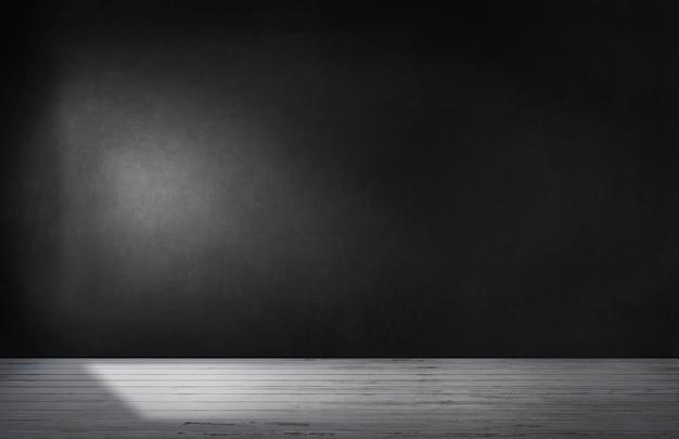 Mur noir dans une pièce vide avec sol en béton
