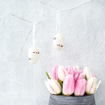 Mur de pâques avec des œufs et des tulipes roses.