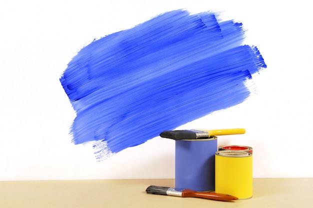 Mur partiellement peint avec peinture et pinceaux
