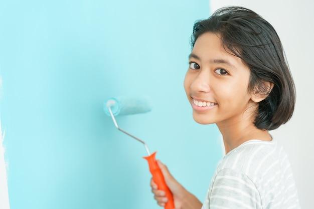 Mur de peinture asiatique fille avec le rouleau à peinture
