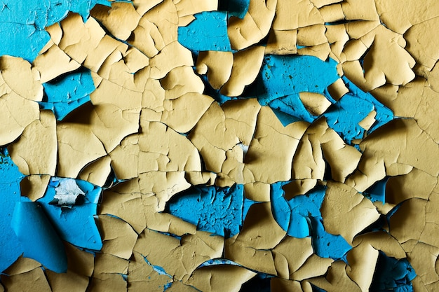 Mur avec de la peinture jaune et bleue dans les fissures. photo de haute qualité
