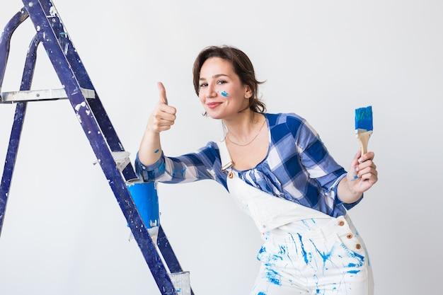 Mur de peinture de jeune femme heureuse à la maison, nous montrant les pouces vers le haut.
