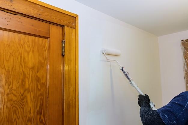 Mur de peinture de travailleur dans la chambre, rénovation d'appartement, maison de réparation d'un rouleau à peinture