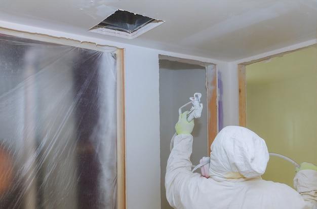 Mur de peinture travailleur avec pistolet de pulvérisation de couleur blanche.